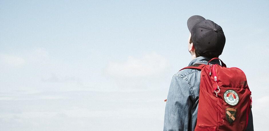 Mann mit rotem Rucksack schaut in den Himmel