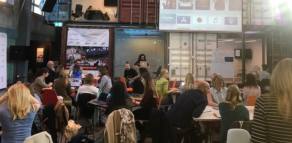 Menschen an Tischen mit Computer in einem Industriegebäude