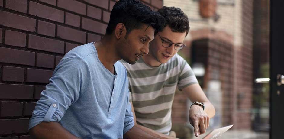 Zwei Männer am Laptop diskutieren