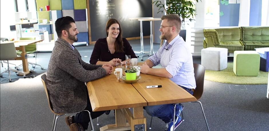 drei Menschen am Tisch am diskutieren