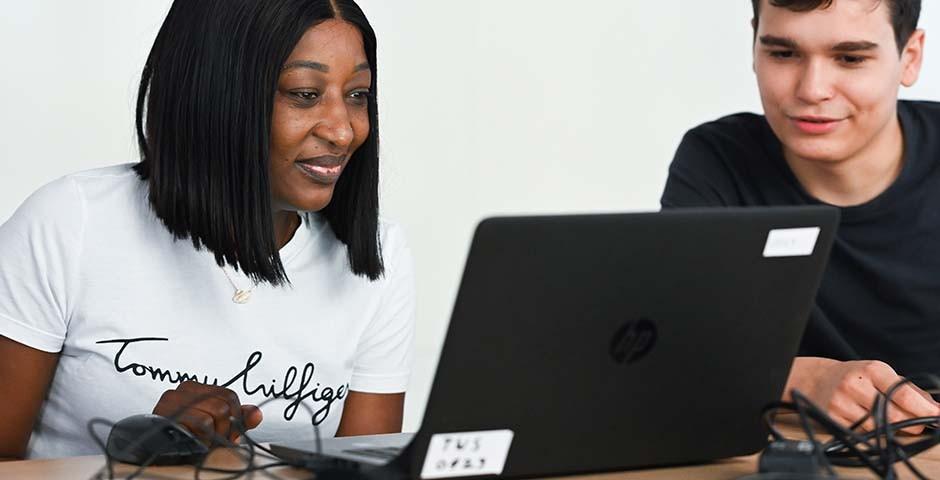 Junge Leute sitzen an einem Tisch, vor ihnen ein Laptop