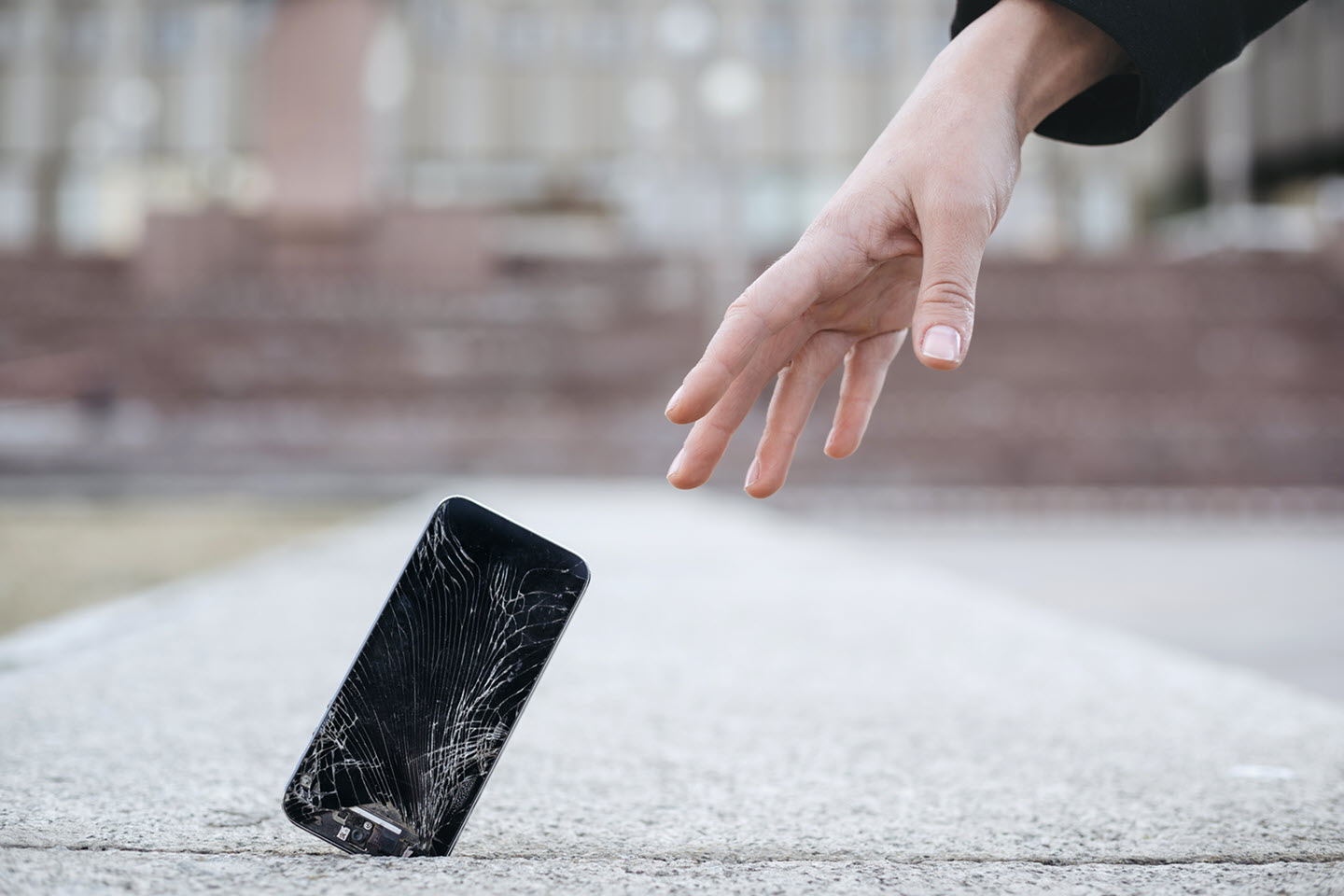 Close up of young woman reaches out to her broken smartphone with cracked screen glass