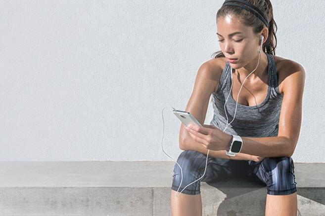 Frau beim Sport schaut aufs Handy