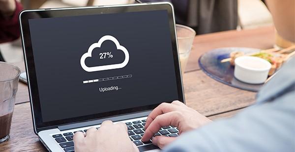 Un uomo carica dati su un computer portatile
