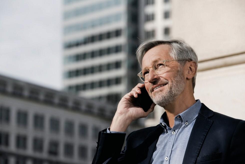 Businessmann mit grauen Haaren und Brille spricht in ein Smartphone