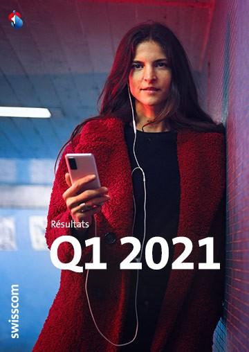 Femme debout contre un mur avec un téléphone portable à la main