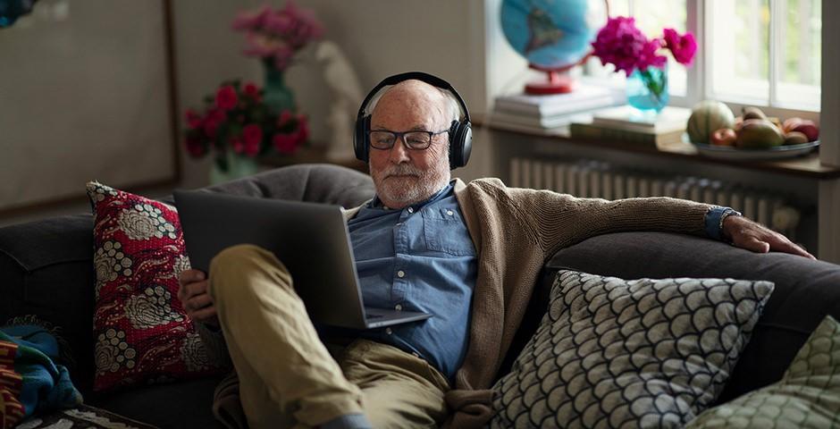 alter Mann mit Kopfhörer und Laptop