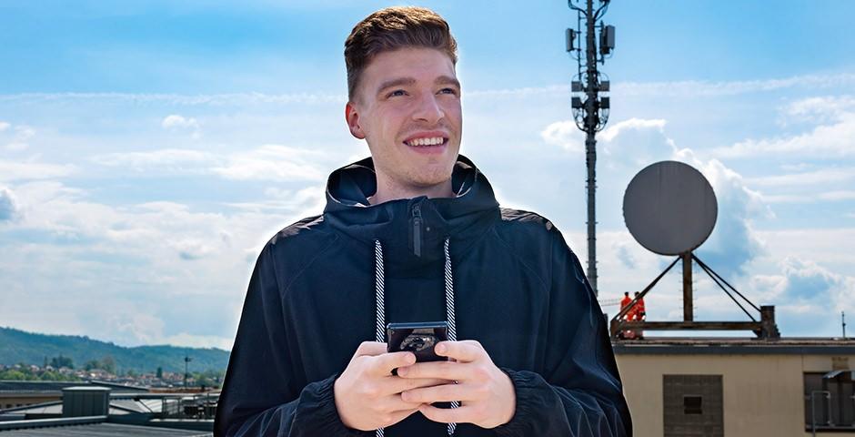 Junger Mann auf Hausdach, im Hintergrund eine Mobilfunk-Antenne