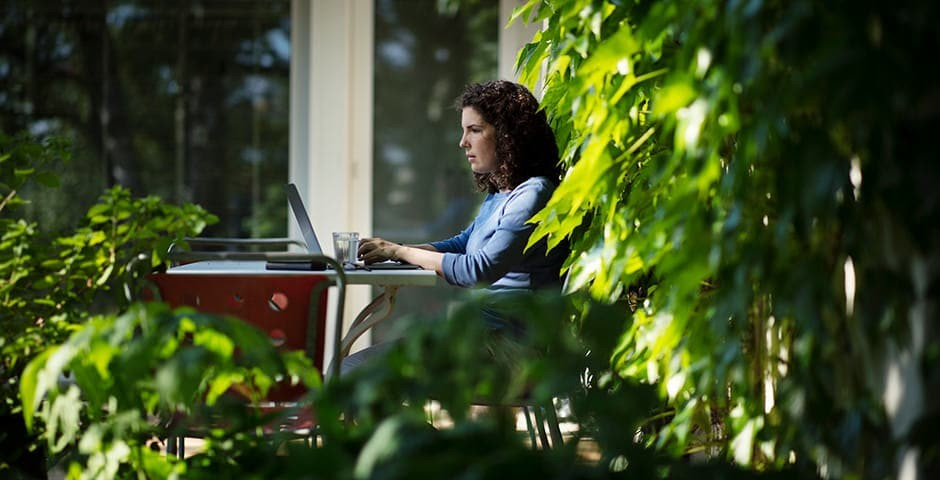 Eine Frau sitzt draussen im Garten an einem Tisch, vor ihr der Laptop und ein Glas Wasser.
