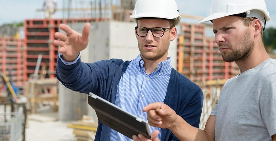 Zwei Männer mit Sicherheitshelmen auf Baustelle. Sie sprechen zusammen, zeigen mit den Händen in die Ferne.