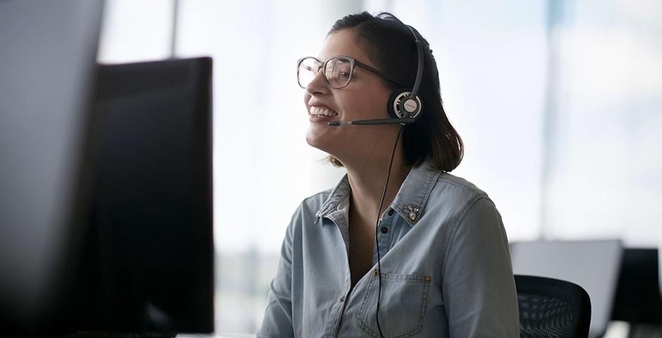 Eine Frau mit Headset blickt auf einen Comutermonitor