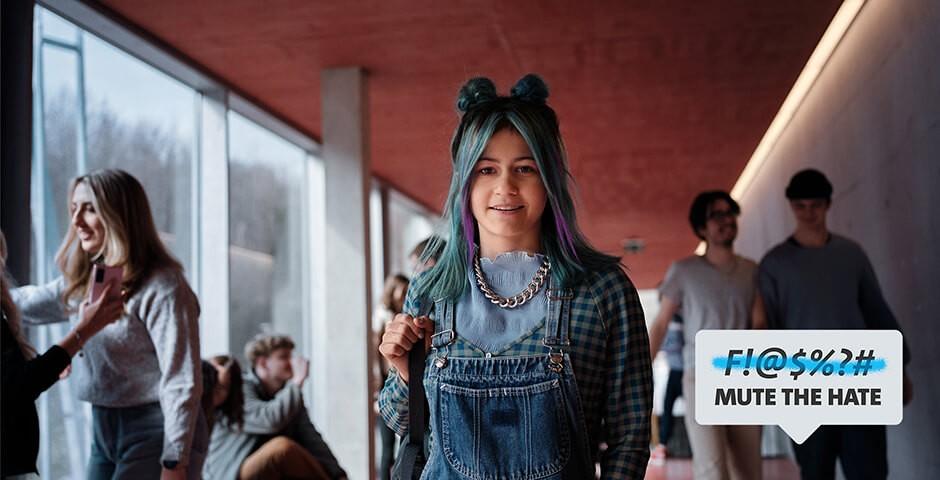 Junge Frau in Latzhosen und mit farbigen Haaren