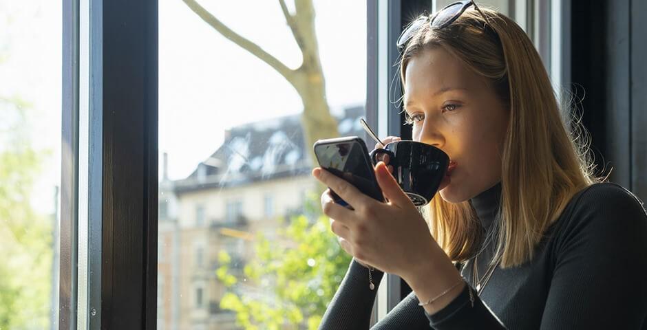 junge Frau mit Mobiltelefon in der Hand