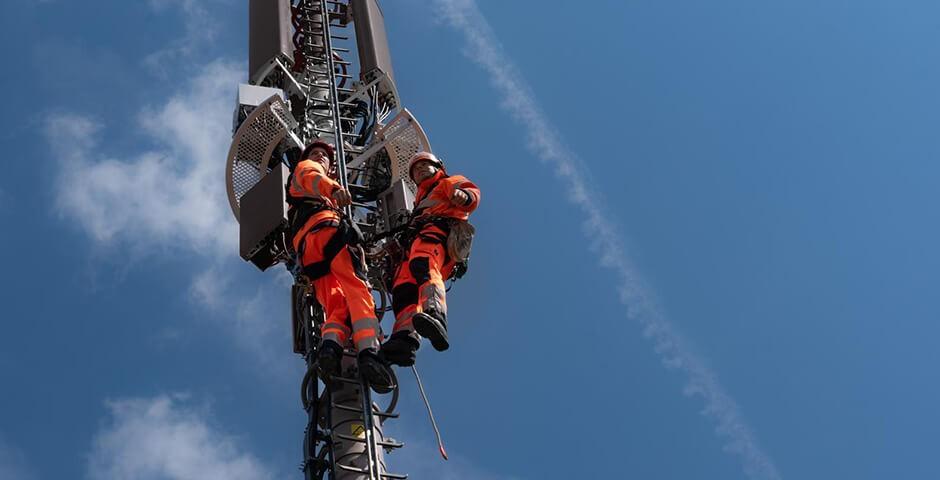 Arbeiter auf Mobilfunk-Antenne