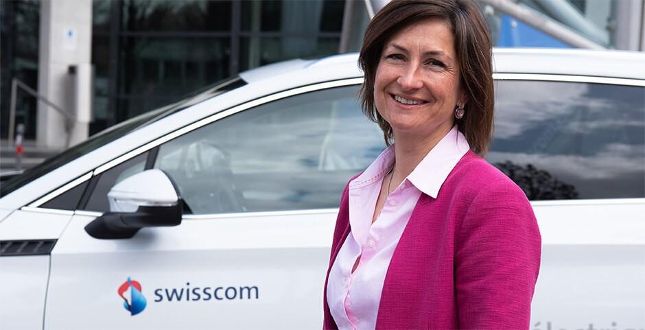 Frau mit lachendem Gesicht vor weissem Auto und Gebäude