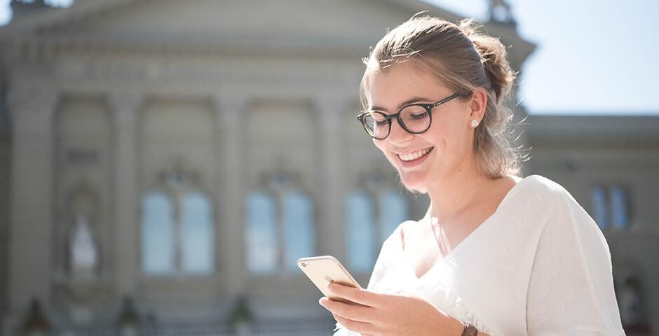 Freut sich, dass sie Ruhe vor unerwünschten Werbeanrufen hat: Frau vor dem Bundeshaus in Bern