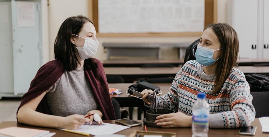 Zwei diskutierende Frauen mit Masken.