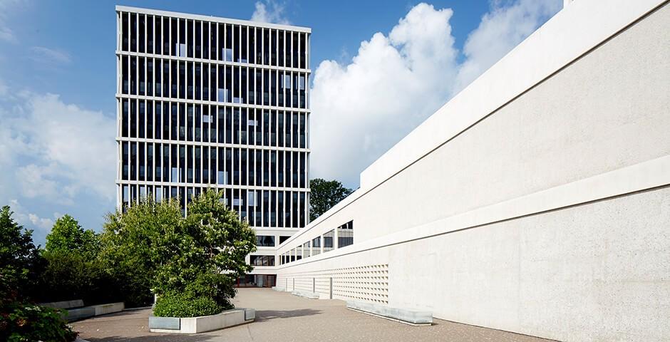 L'immagine mostra il palazzo del Tribunale federale di San Gallo. Il cielo è blu con nubi bianche e l'edificio è grigio e bianco. Davanti all'edificio si vedono alberi e cespugli. L'edificio in sé è un moderno grattacielo con tante grandi finestre.