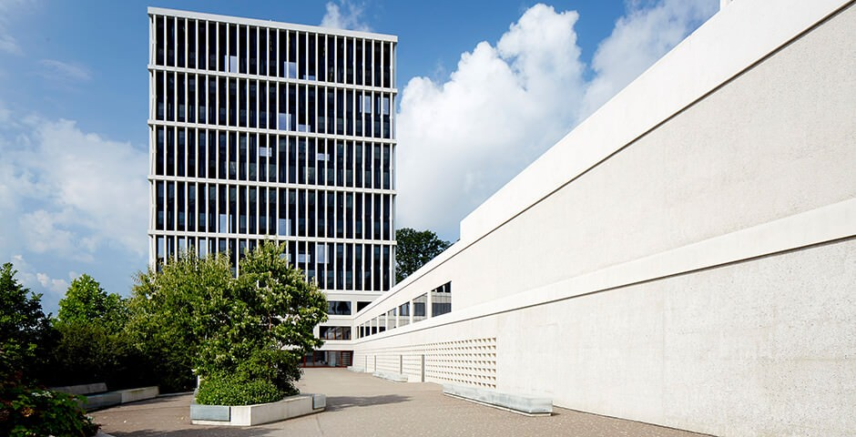 Photo shows the Federal Administrative Court building in St. Gallen. The sky is blue with white clouds and the building is grey/white. In front of the building, you can see trees and shrubs. The building itself is a modern high-rise building with many large windows.