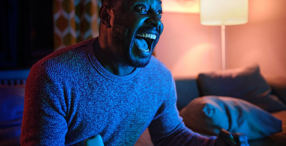 Un homme exulte devant sa télévision.