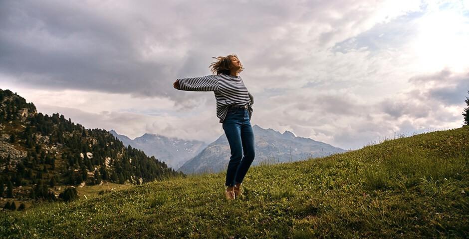 Junge Frau geniesst mit ausgebreiteten Armen die Natur auf einer Alpwiese