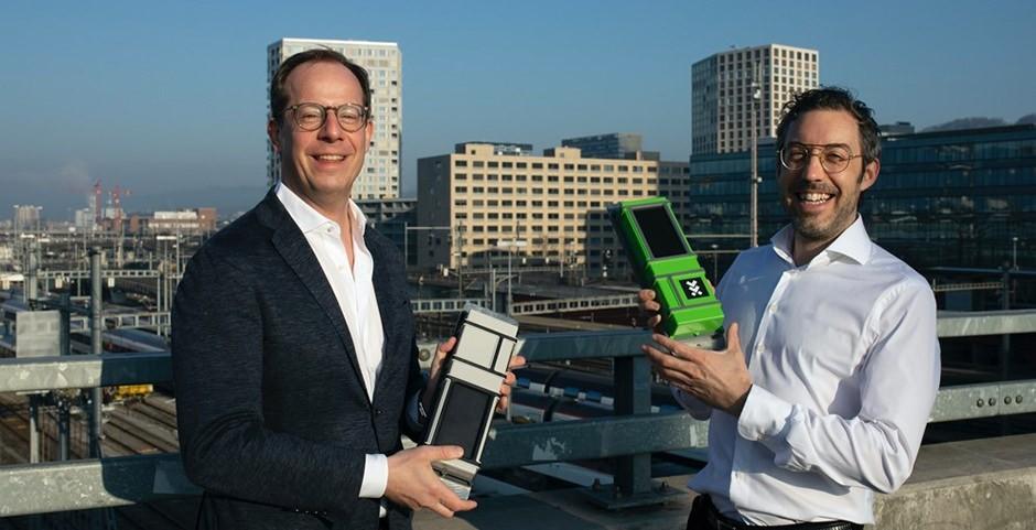 Zwei Männer auf Eisenbahnbrücke mit IoT Geräten in den Händen