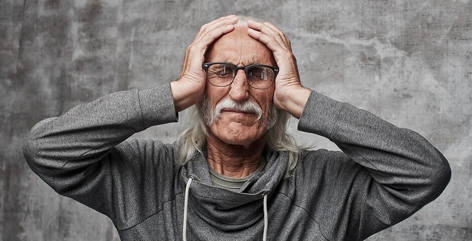 Mann mit geschlossenen Augen hält sich den Kopf mit beiden Händen