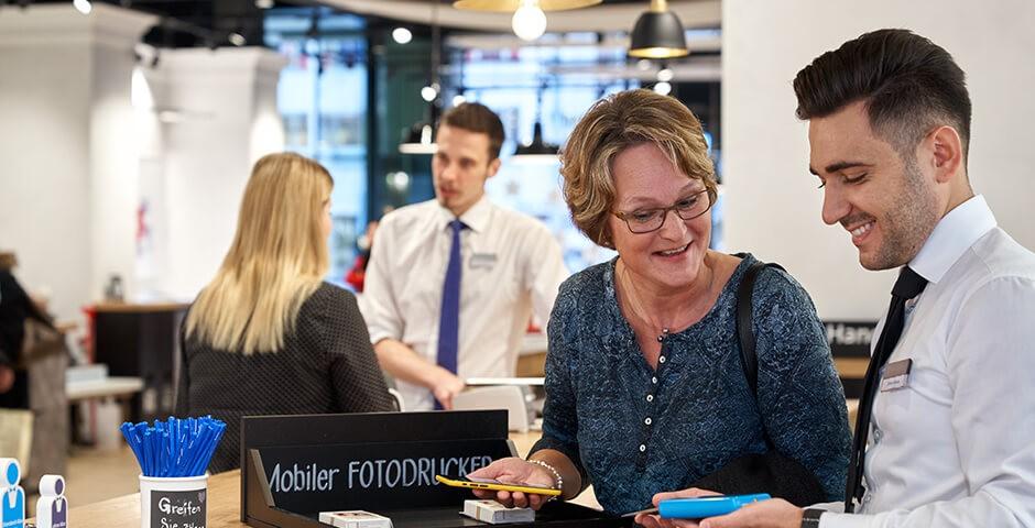 Ein Mitarbeiter mit einem Kunden im Swisscom Shop
