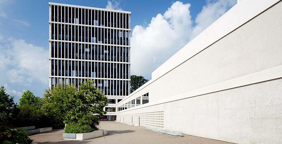 L'image montre le bâtiment du Tribunal administratif fédéral à Saint-Gall. Le ciel est bleu avec des nuages blancs et le bâtiment est gris/blanc. Des arbres et des buissons sont visibles devant le bâtiment. Le bâtiment lui-même est un immeuble moderne avec beaucoup de grandes fenêtres.