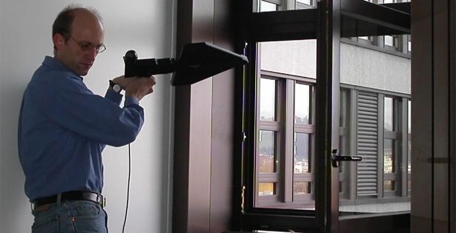 Mann mit Messgerät am Fenster