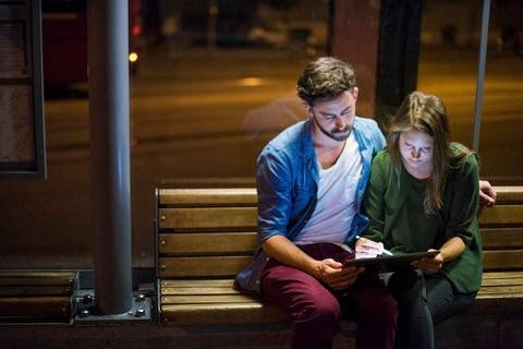 Paar sitzt an Bushaltestelle