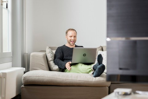 Mann mit Laptop auf Sofa