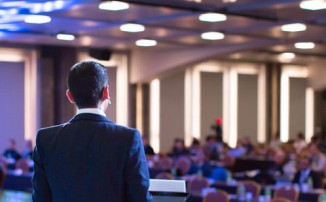 Speaker giving a talk at a corporate business conference. Audience in hall with presenter in front of presentation screen. Corporate executive giving speech during business and entrepreneur seminar.