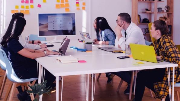 Personen sitzen am Tisch und schauen auf Monitor