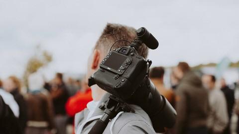 Un homme porte un appareil photo sur son épaule