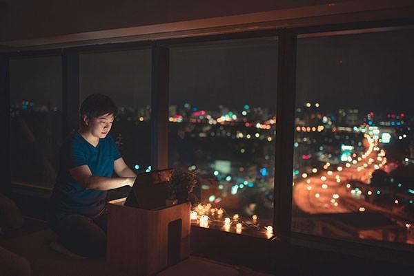 Mann mit Laptop vor Fenster