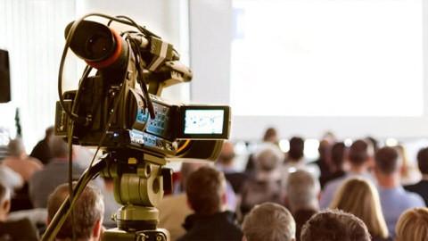 Une caméra pointée sur le public