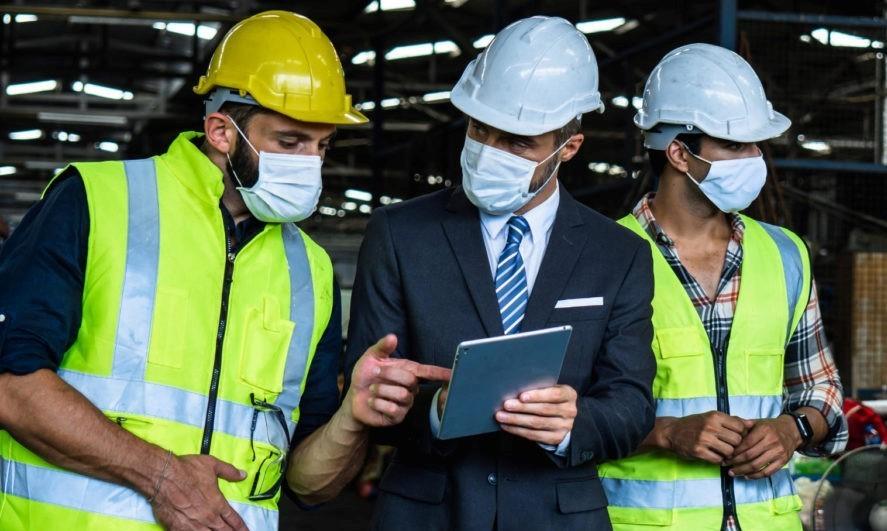 Industrial engineer in suite and safety helmet working in factory