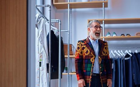 Un domo indossa una giacca colorata in un negozio