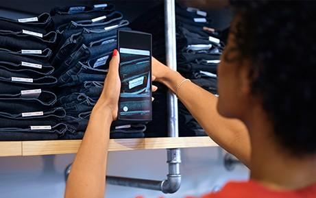 Dispositivo di cassa mobile scansiona il codice a barre di un paio di jeans