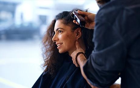 Frau lässt sich von Coiffeur die Haare schneiden