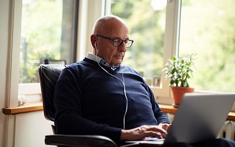 Älterer Mann surft am Laptop und trägt Kopfhörer