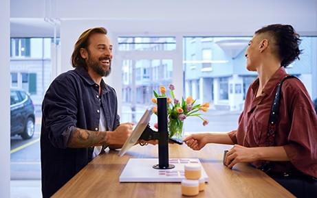 Una cliente paga al venditore con metodo contactless al bancone