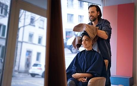 Un coiffeur sèche les cheveux d'une cliente