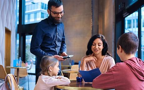 Bedienung nimmt am Tisch die Bestellung auf Kassengerät auf