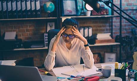 gestresste Frau an Schreibtisch